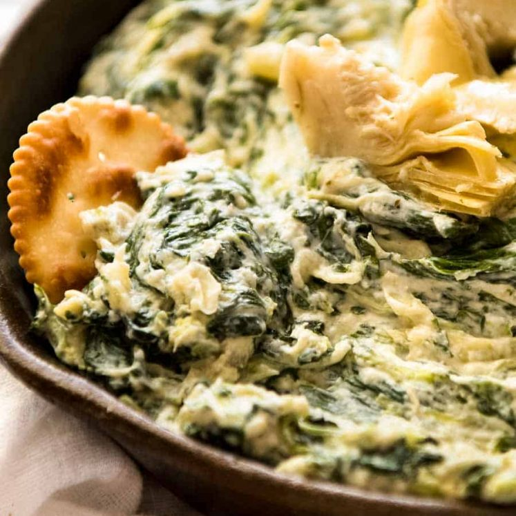 Close up of ritz cracker scooping up Spinach Artichoke Dip in a rustic black dish