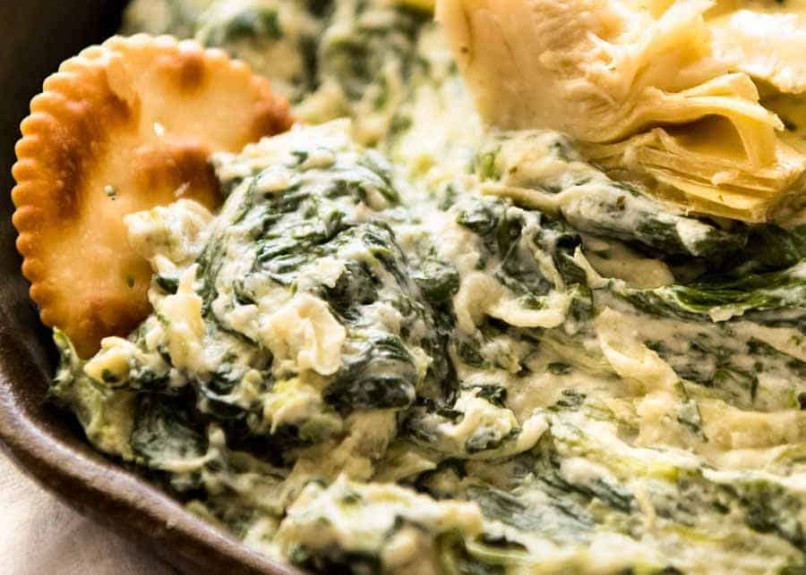 Close up of ritz cracker scooping up Spinach Artichoke Dip