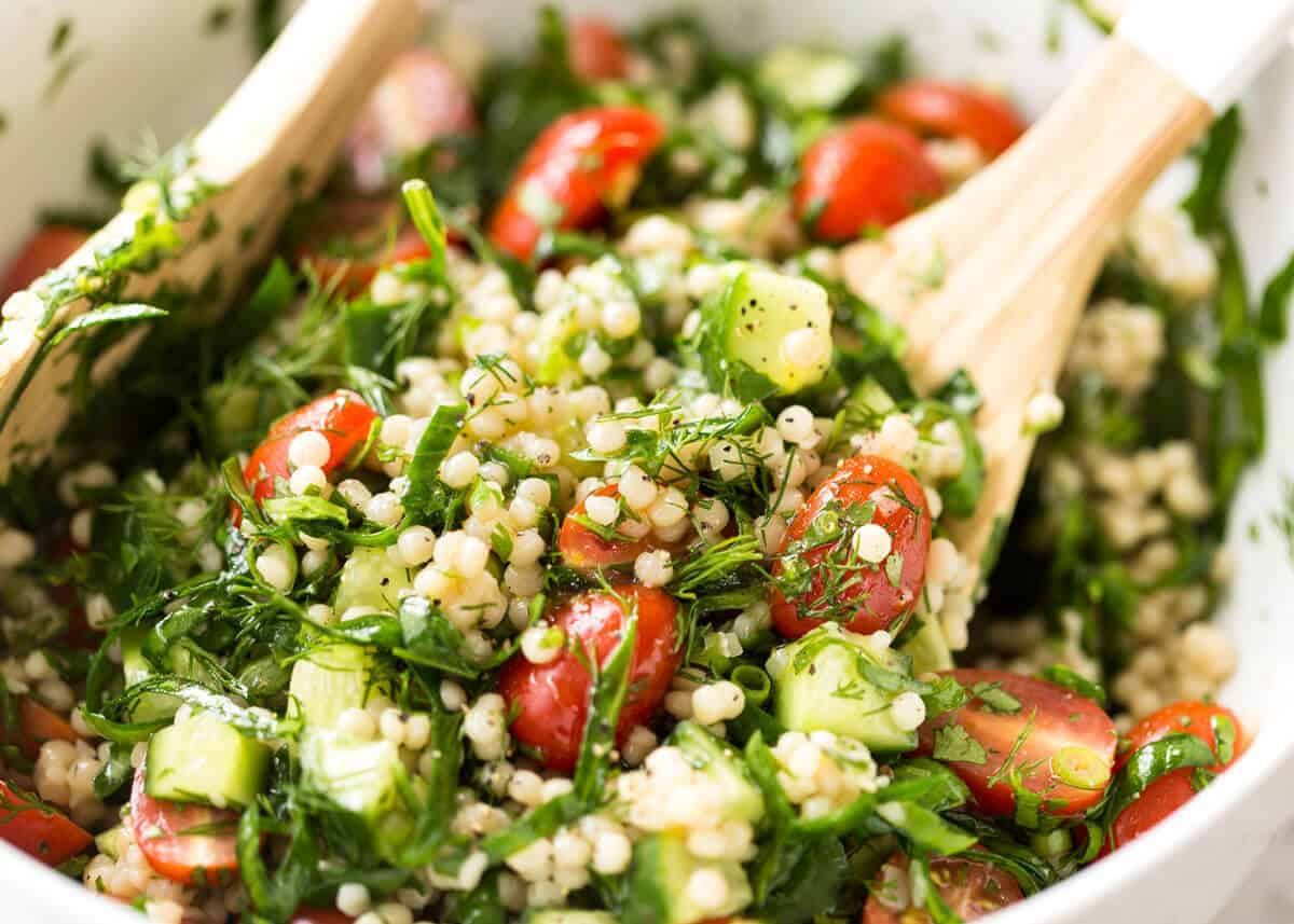 This Israeli Couscous Salad is fabulously addictive! Tender, flavour infused beads of couscous tossed with spinach, tomato, cucumber, herbs and a fresh lemon dressing. Summer in a bowl! recipetineats.com