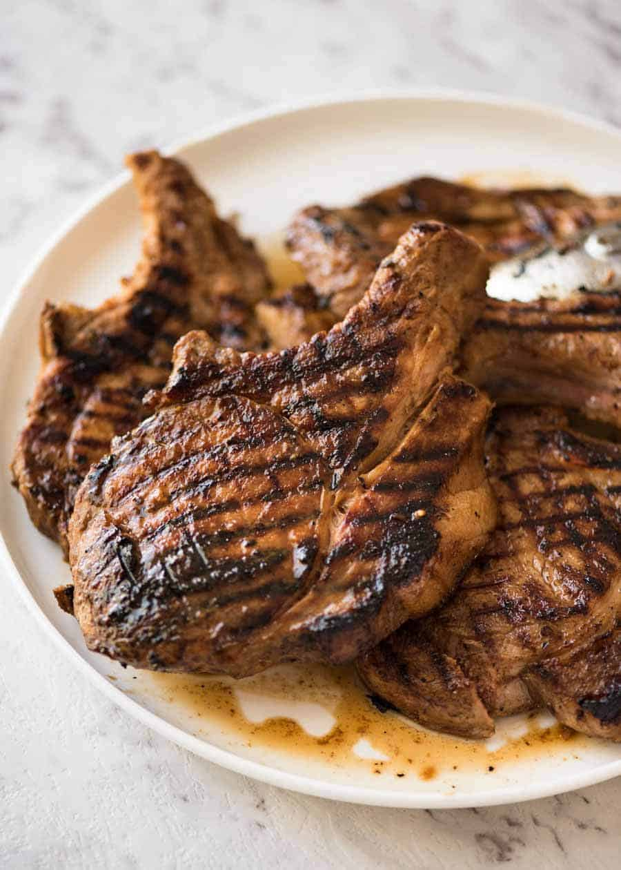Pile of grilled chops on a white plate, made using made using a great Pork Chop Marinade