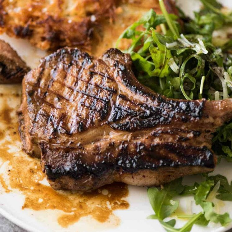 Overhead photo of Grilled chops on a plate with potato rosti and salad, made using amade using a great Pork Chop Marinade