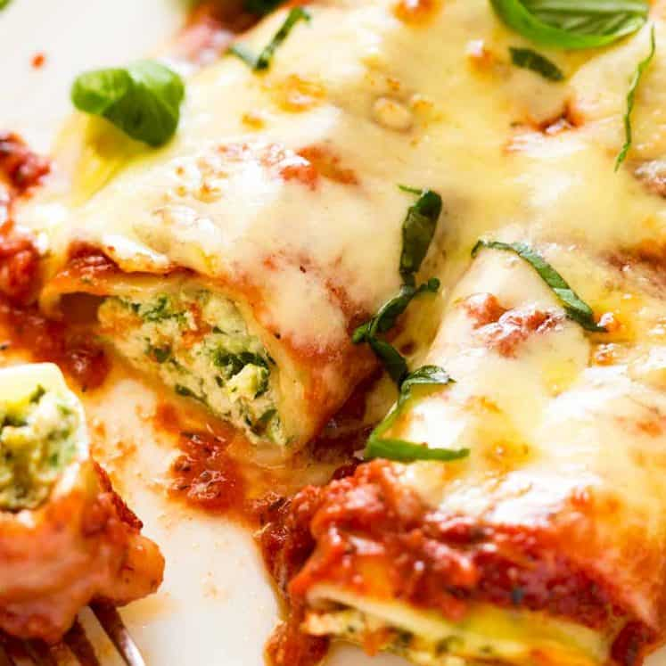 Close up photo of 2 pieces of Spinach and Ricotta Cannelloni with tomato pasta sauce on a plate
