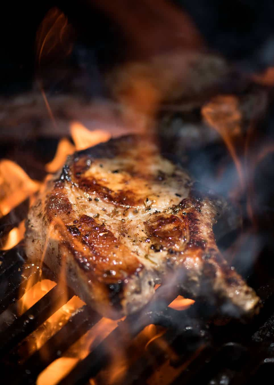 Lemon Garlic Marinated Grilled Pork Chops on the barbecue being licked by flames.