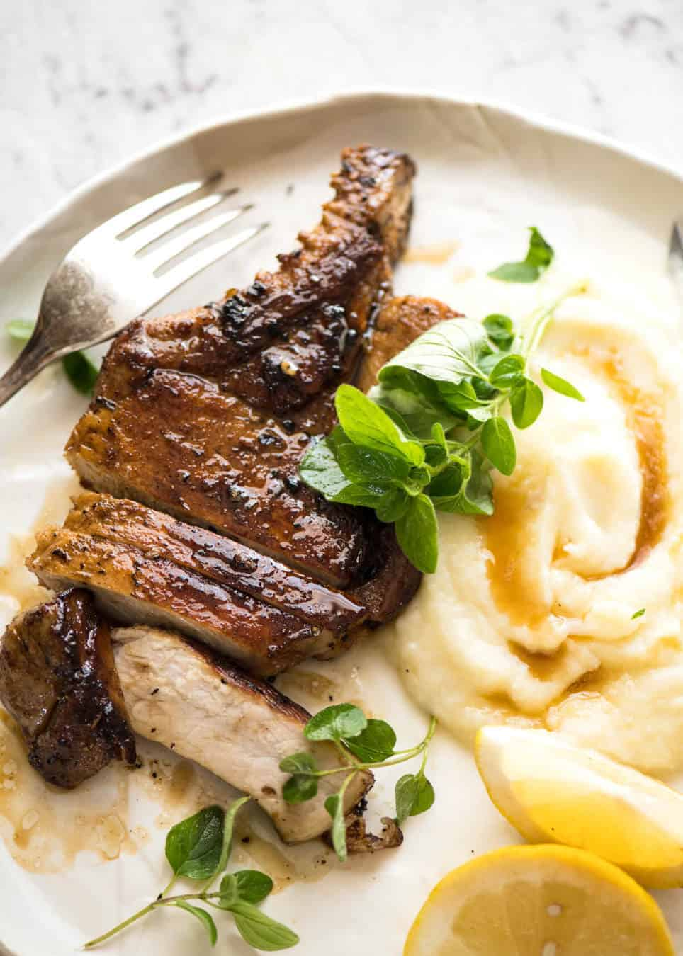 Lemon Garlic Marinated Grilled Pork Chops on a white plate with mashed potato on the side.