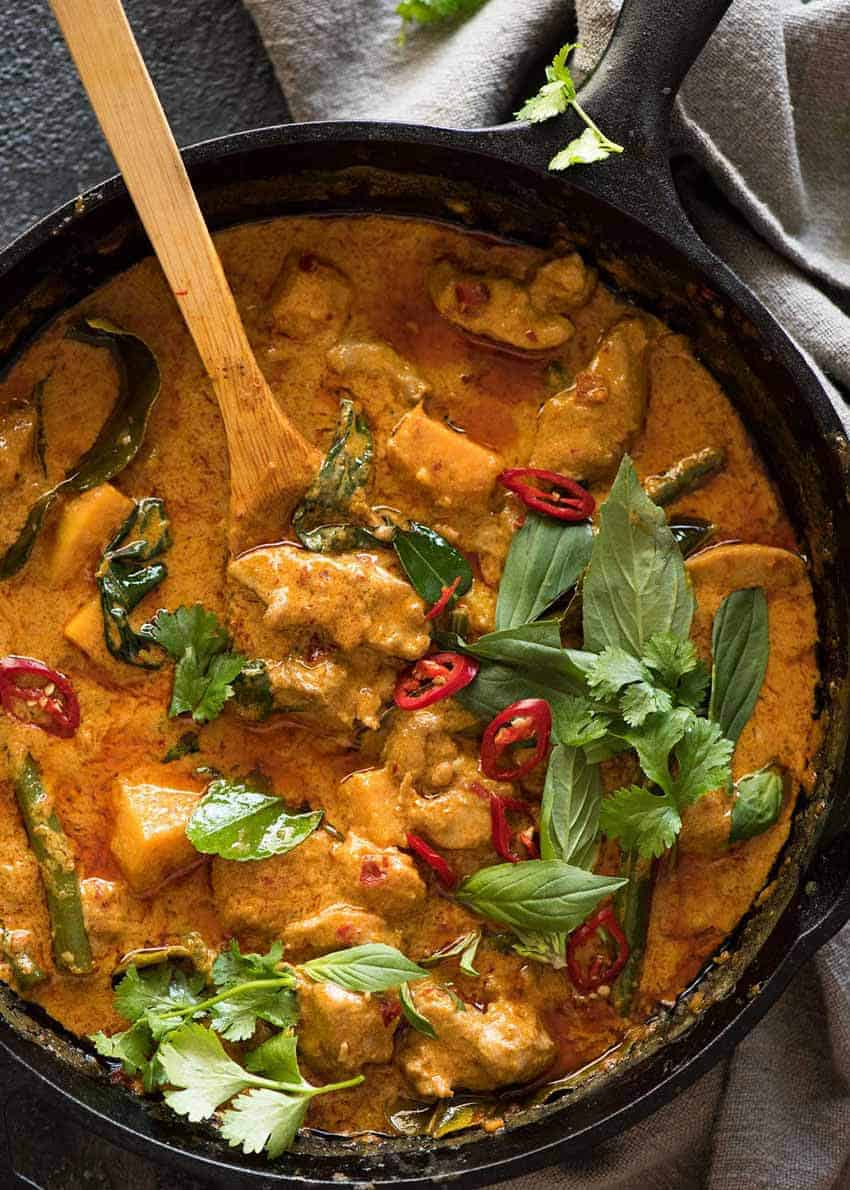 Overhead photo of Thai Red Curry with Chicken in a black skillet, fresh off the stove.