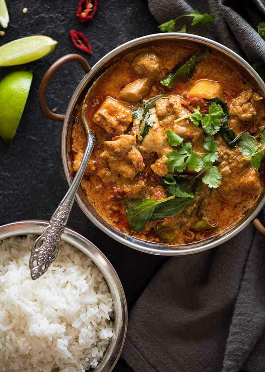 Thai Red Curry with Chicken in a serving bowl with a side of rice, ready to be served.
