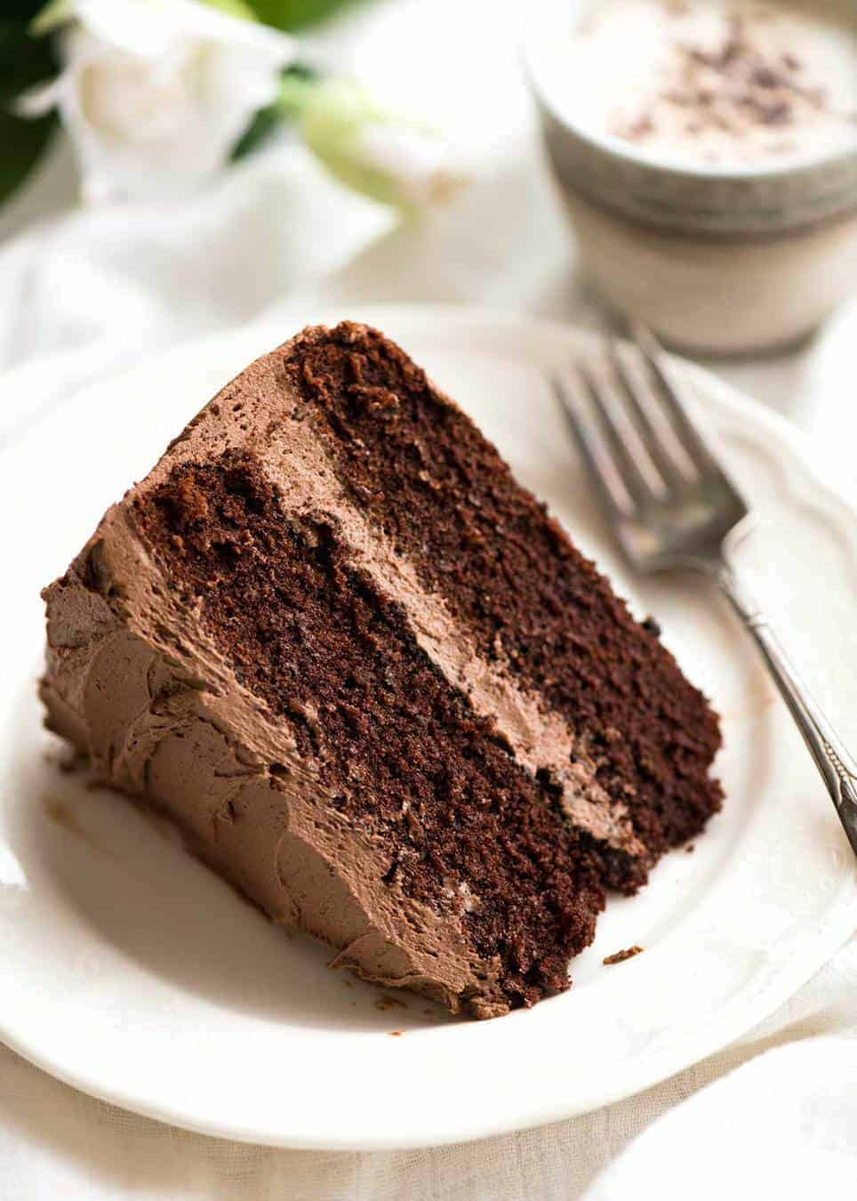 A slice of Chocolate Cake with Chocolate Buttercream Frosting on a white dessert plate with a fork, ready to be eaten.