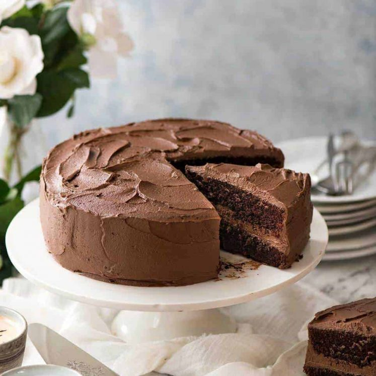 A moist Chocolate Cake with Chocolate Buttercream Frosting on a white cake platter with a slice cut and partially pulled out and a stack of dessert plates next to it.