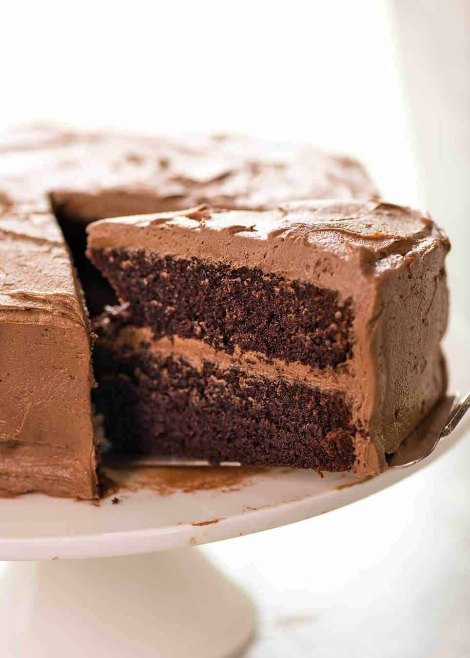 A photo showing half a Chocolate Cake frosted with Chocolate Buttercream on a white cake stand with a large slice partially pulled out.