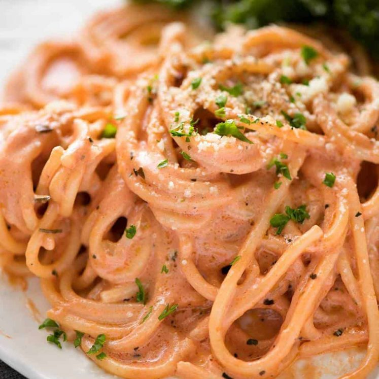 Creamy tomato pasta on a plate with marinated kale salad.