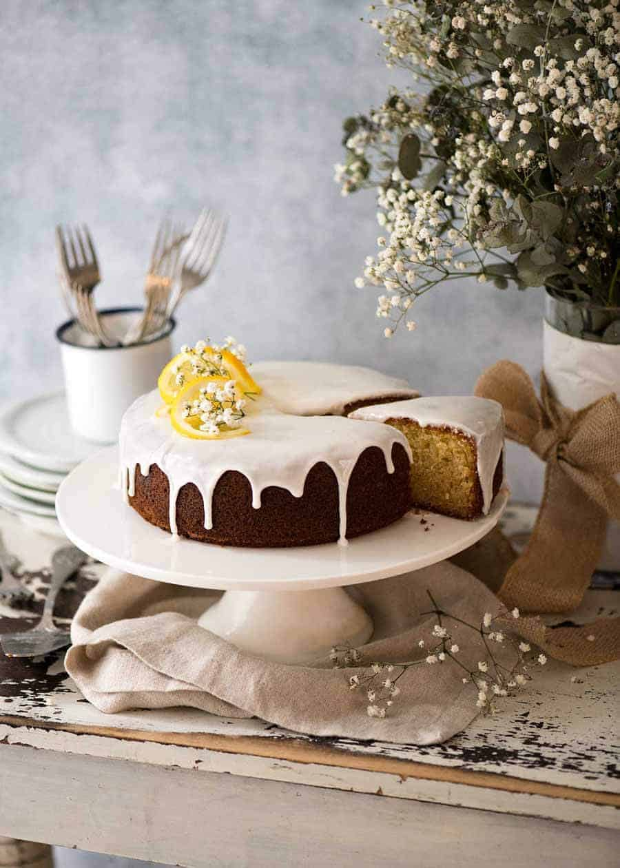 Lemon Cake with drippy lemon glaze on a white cake platter with a piece cut out and plates on the side, ready to the served.