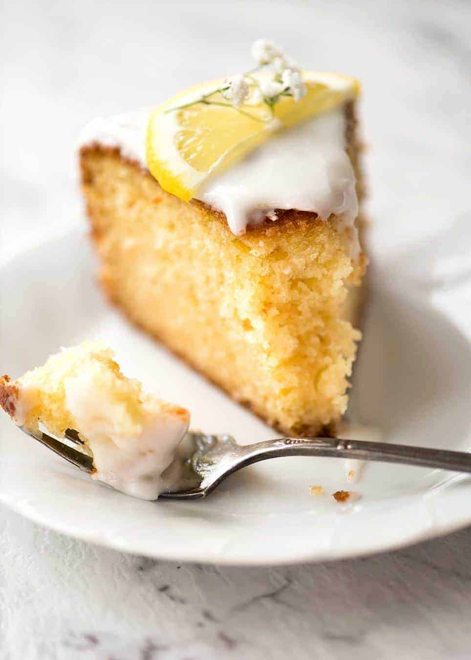 Piece of Lemon Yoghurt Cake with Lemon Glaze on a white plate.