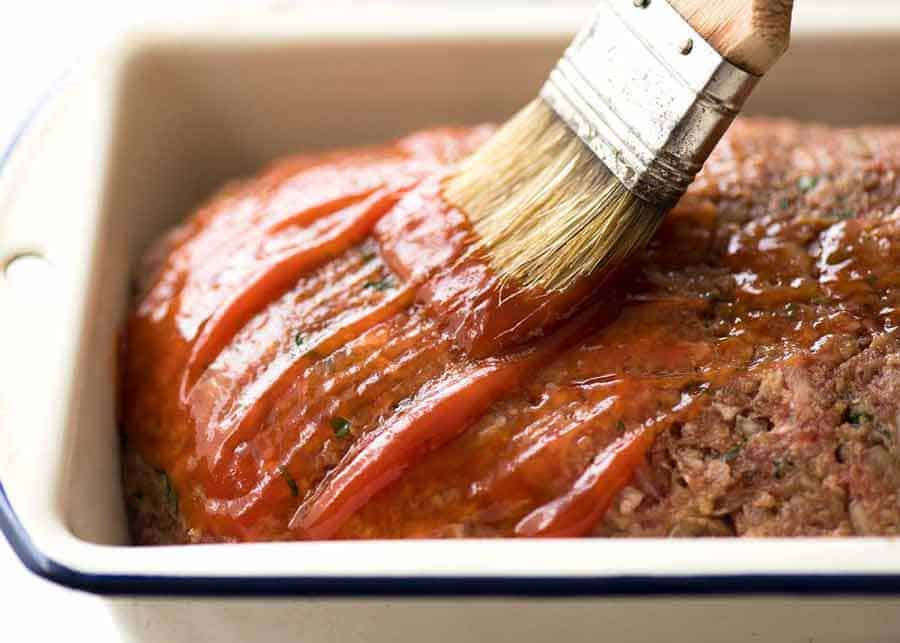 Brushing glaze on meatloaf in pan