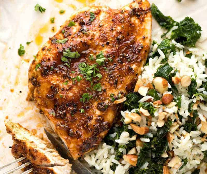 Juicy Oven Baked Chicken Breast on a white plate with a side of Garlic Butter Kale Rice