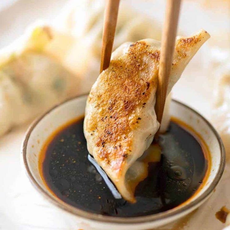 Potsticker being dipped in a small bowl with soy sauce and chilli oil