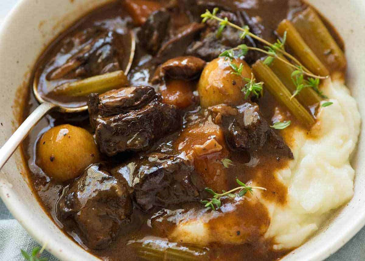 Photo of Beef Stew over mashed potato in a rustic cream bowl.