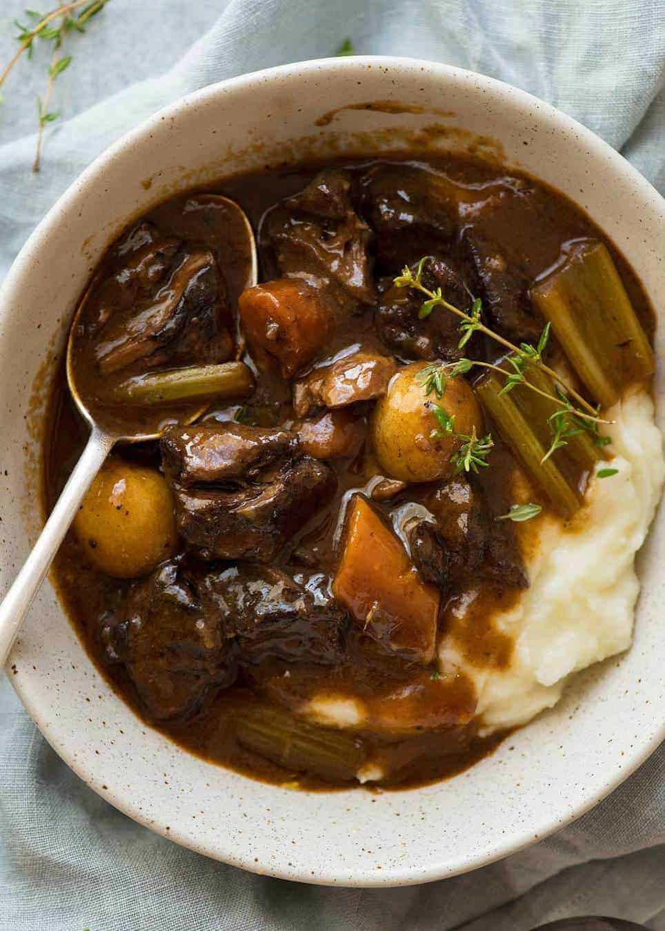 Overhead photo of Beef Stew over mashed potato in a rustic cream bowl.