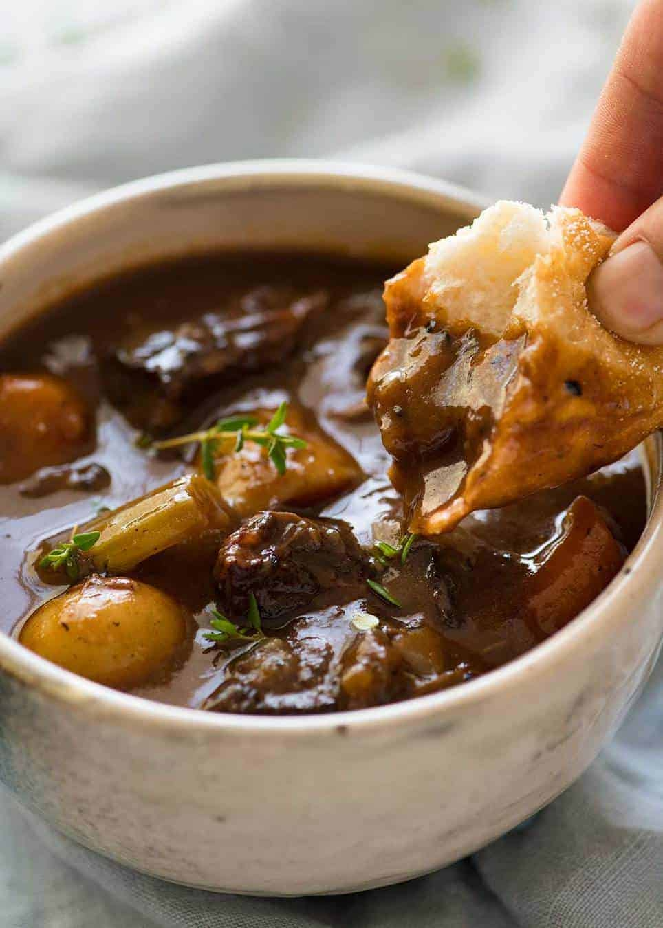 Close up photo of a piece of bread being dunked into Beef Stew with Potatoes and Carrots. The bread shows how thick the gravy sauce is./