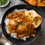 Overhead photo of chicken tikka masala on basmati rice in a dark rustic bowl with a piece of naan wedged in on the side.