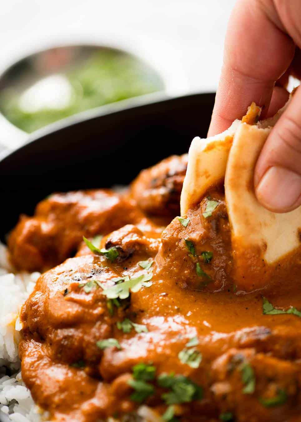Close up of naan bread being used to scoop up some Chicken Tikka Masala.