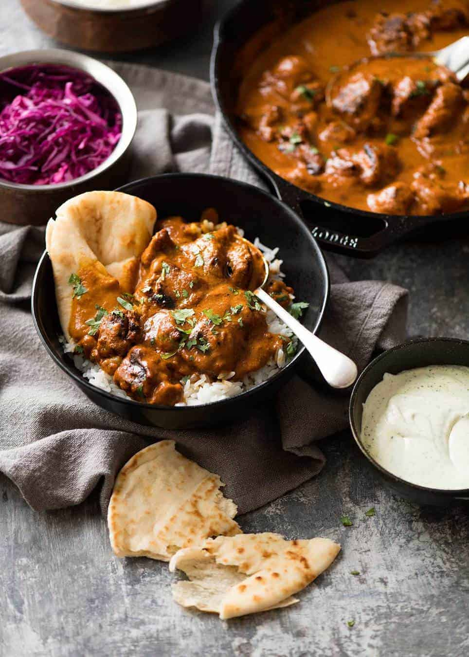 Photo of chicken tikka masala on basmati rice in a dark rustic bowl with a piece of naan wedged in on the side. Pickled red cabbage and skillet of Chicken Tikka Masala in the background.