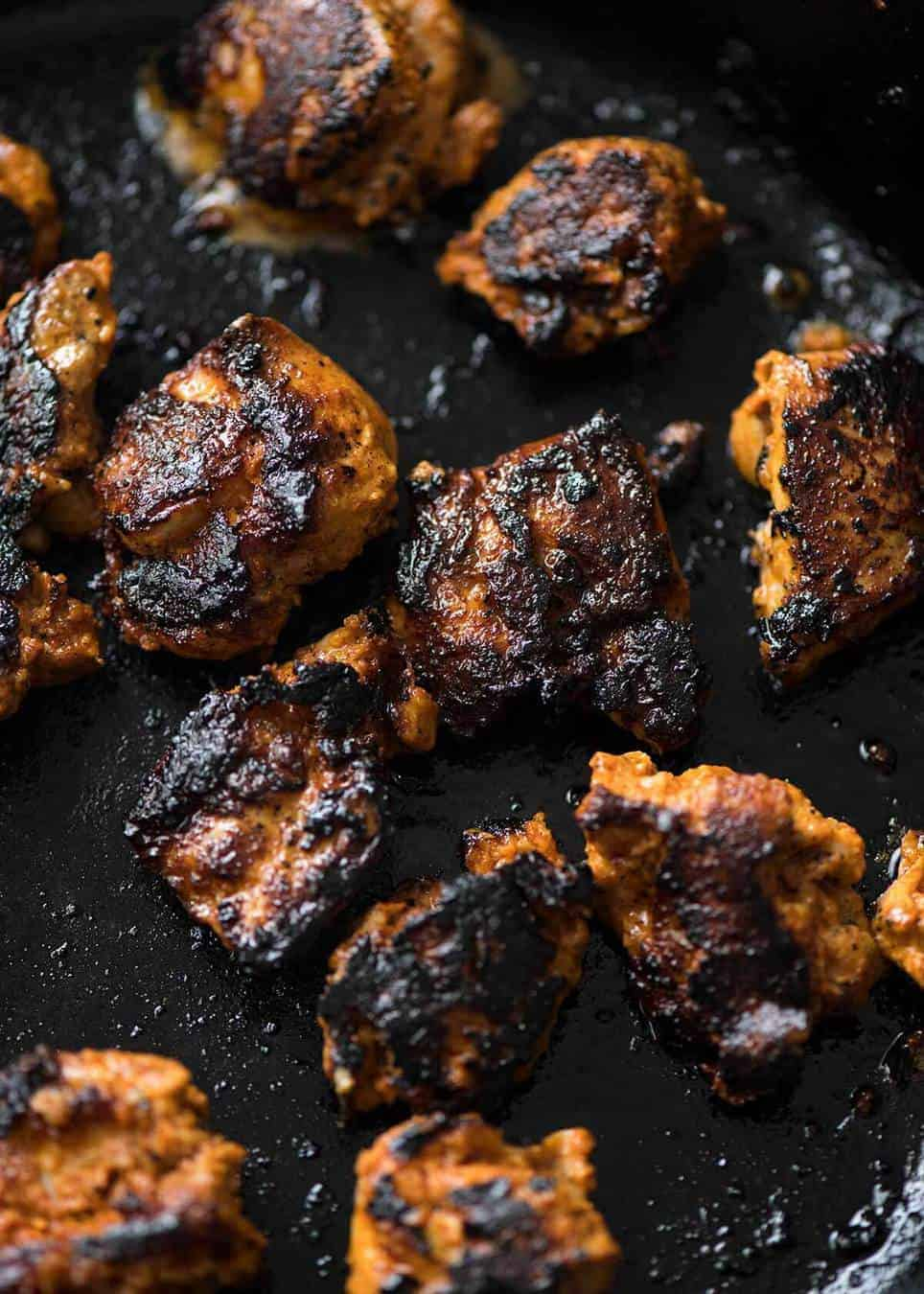 Close up of Chicken Tikka cooking in a black skillet, charred.