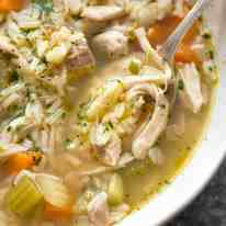 Close up of chicken and rice soup in a rustic beige bowl, ready to be eaten.