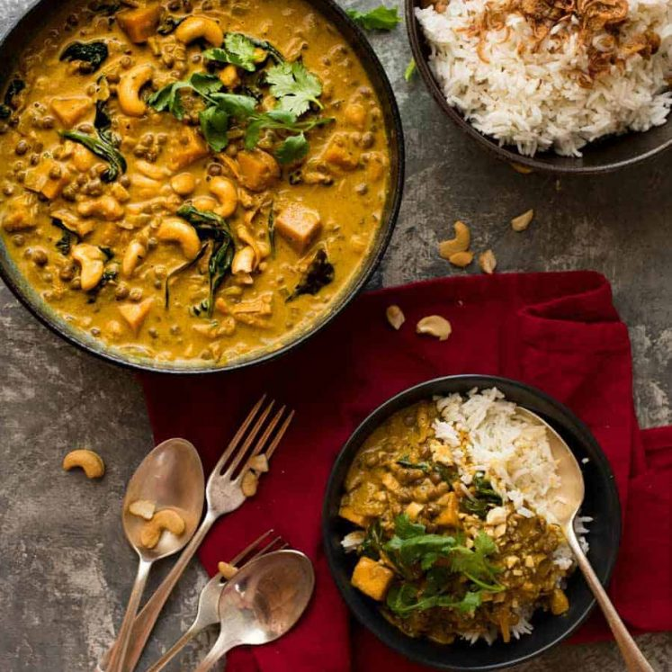 Tablescape overhead photo of Coconut Curry with Lentils & Pumpkin in a dark bowl with a side of rice, ready to be served.