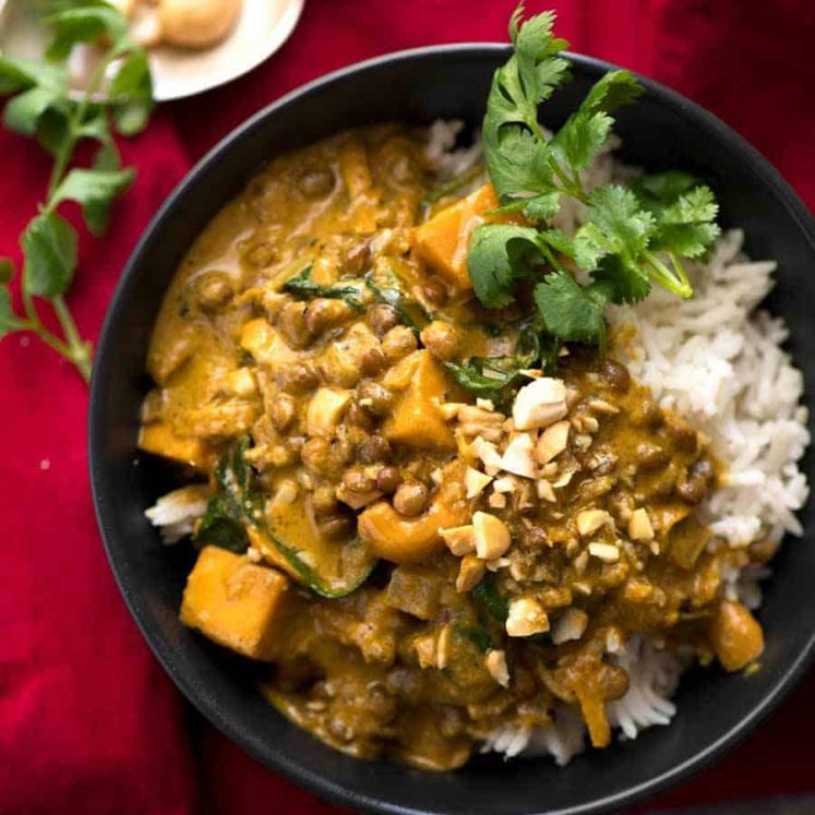 Coconut Curry with Lentils & Pumpkin served over rice in a small black bowl, ready to be eaten.