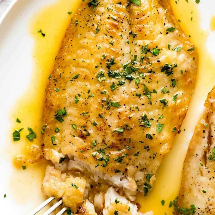 Overhead photo of a crispy pan fried fish fillet drizzled with Lemon Butter Sauce and sprinkled with parsley. On a white plate.