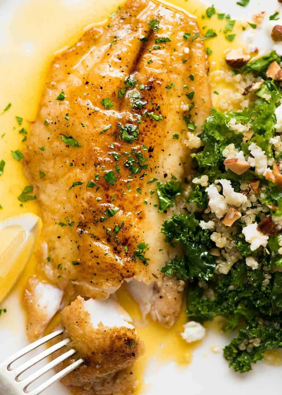 Overhead photo of a crispy pan fried fish fillet drizzled with Lemon Butter Sauce and sprinkled with parsley on a white plate with a side of Kale Quinoa Salad.