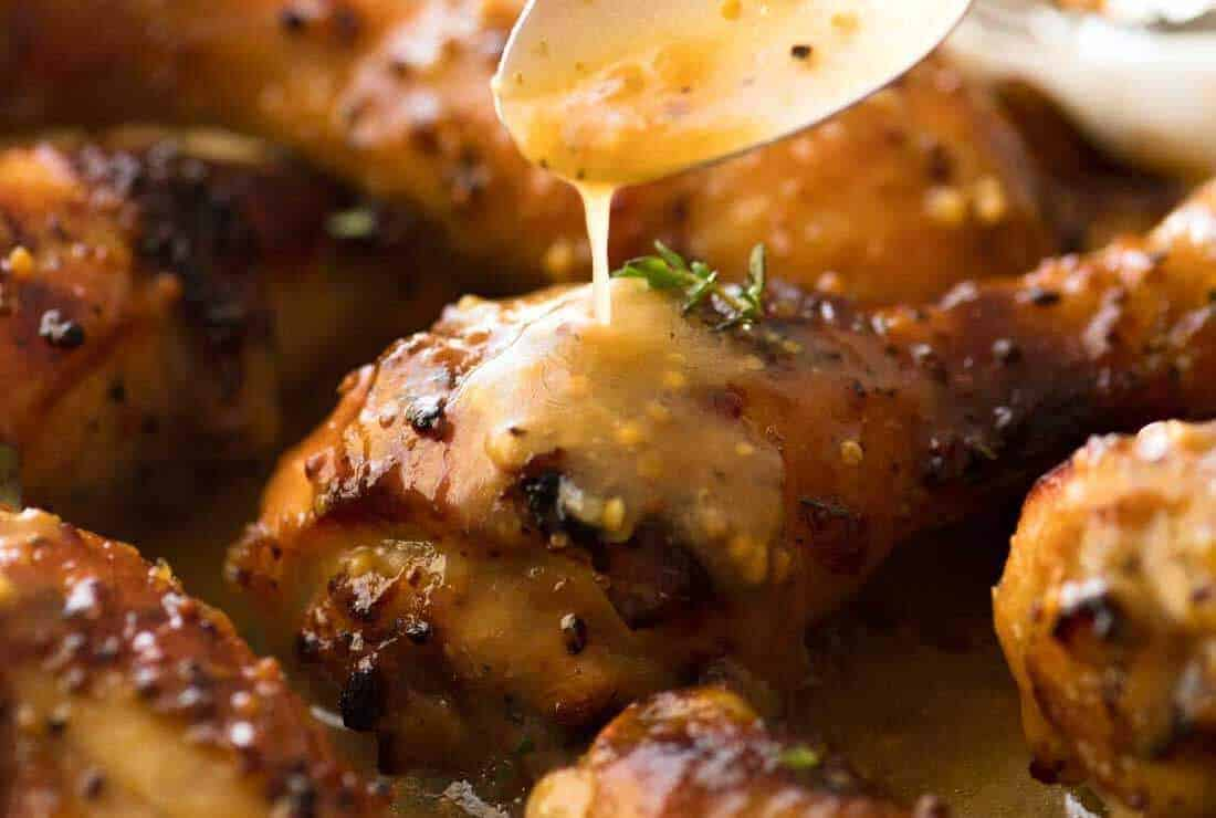 Close up of sticky Honey Mustard Chicken Drumsticks and crispy smashed potatoes, fresh out of the oven.