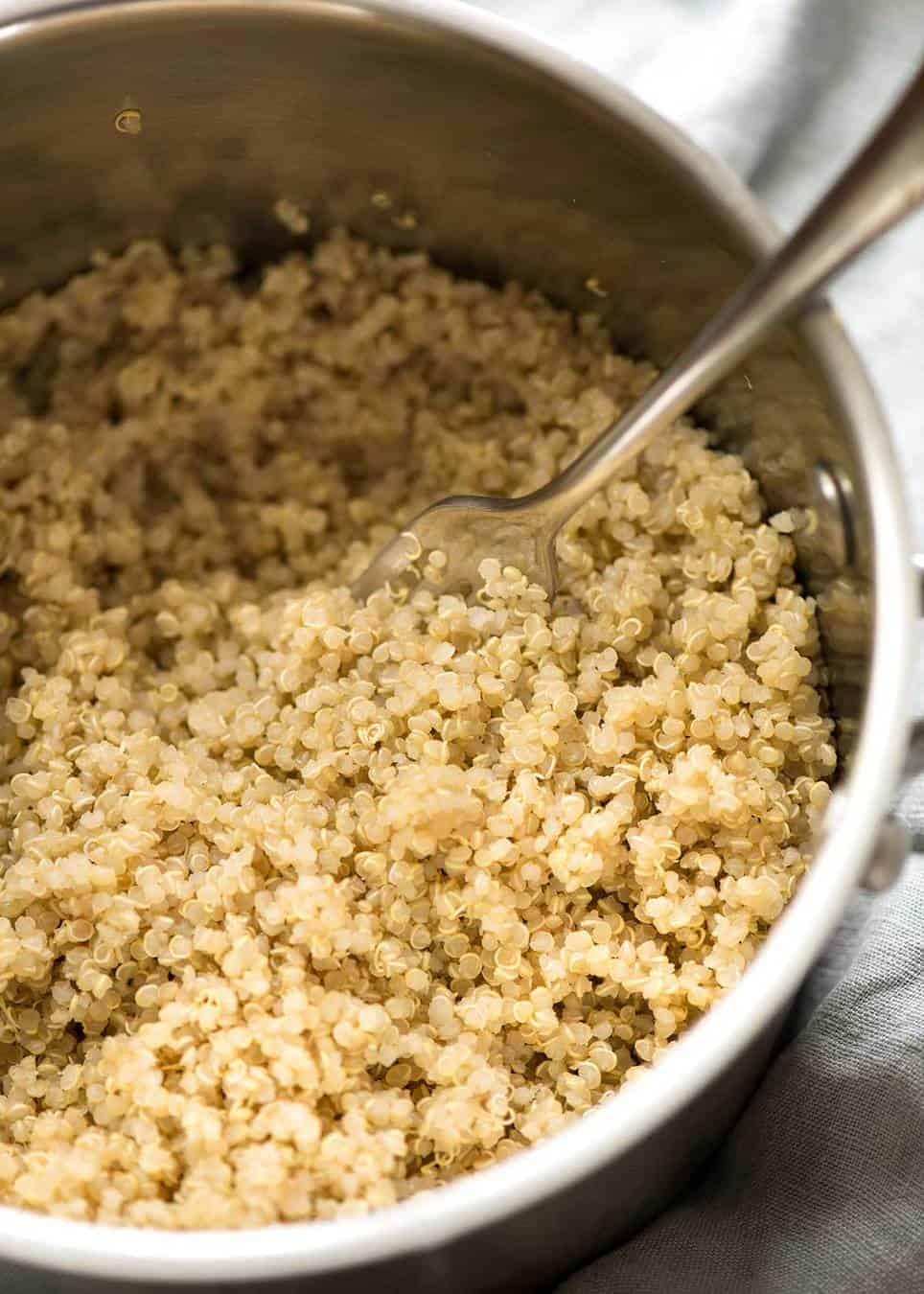 Cooked fluffy quinoa in a silver saucepan.