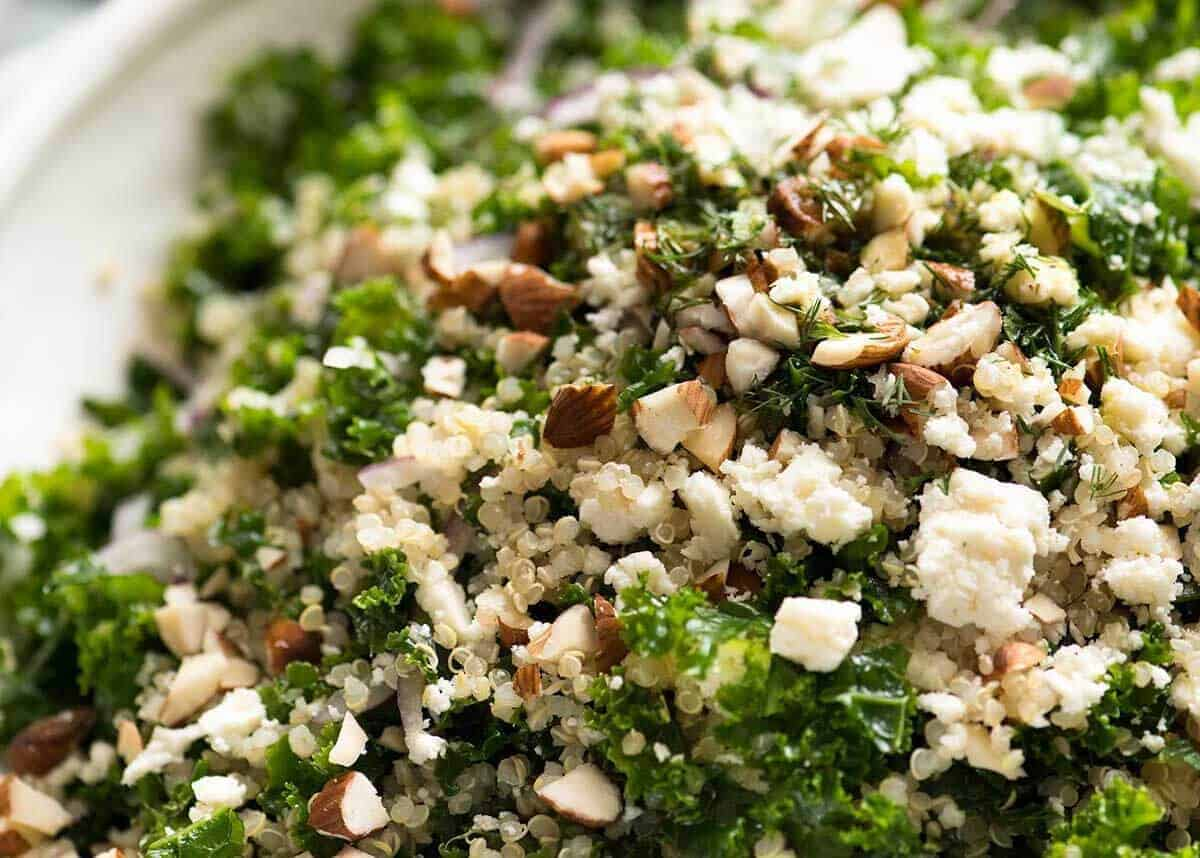 Close up of Kale and Quinoa Salad sprinkled with chopped almonds and feta