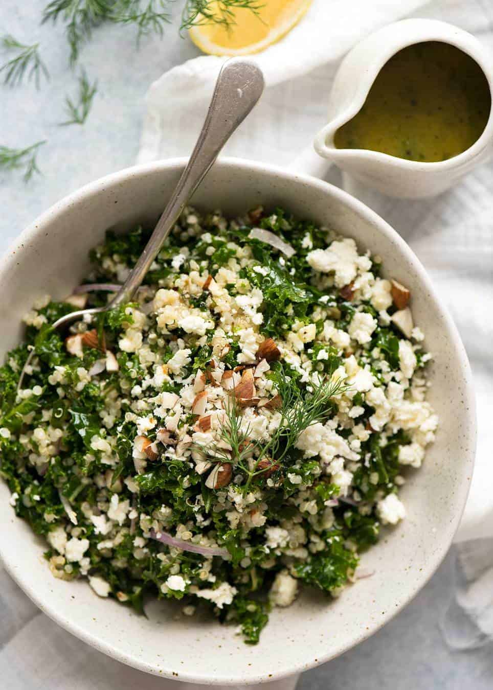Overhead photo of Kale and Quinoa Salad in a white rustic salad bowl with a small jug of lemon dressing on the side.