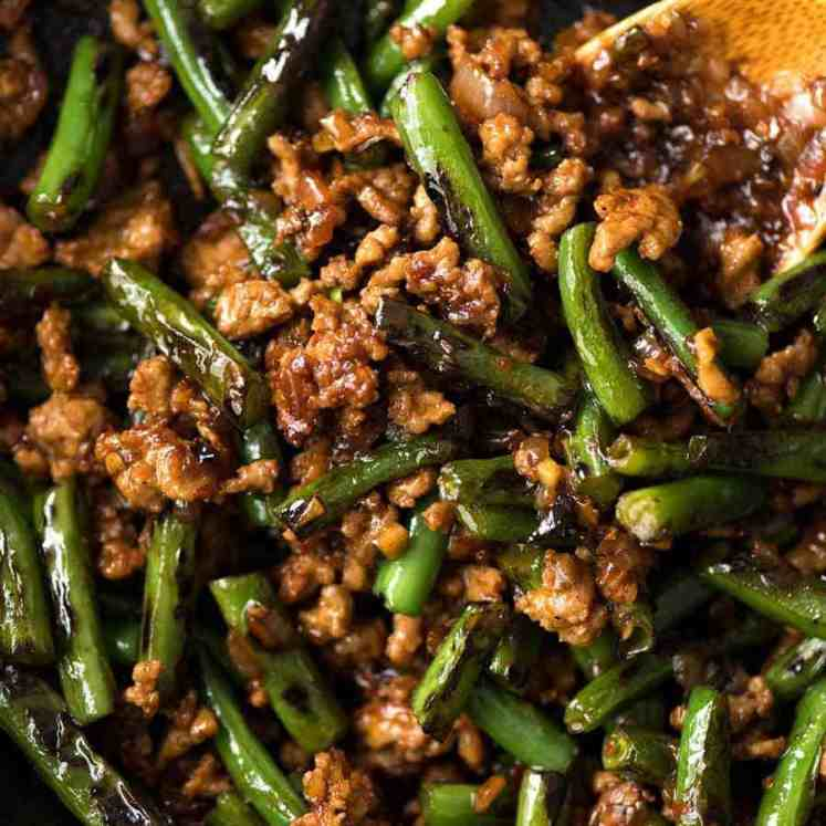 Close up of Pork Stir Fry with Green Beans in a black skillet, fresh off the stove