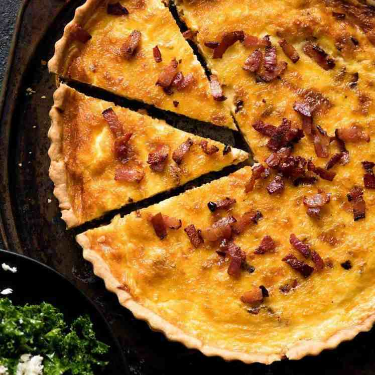 Overhead photo of a golden Quiche Lorraine with 2 pieces cut
