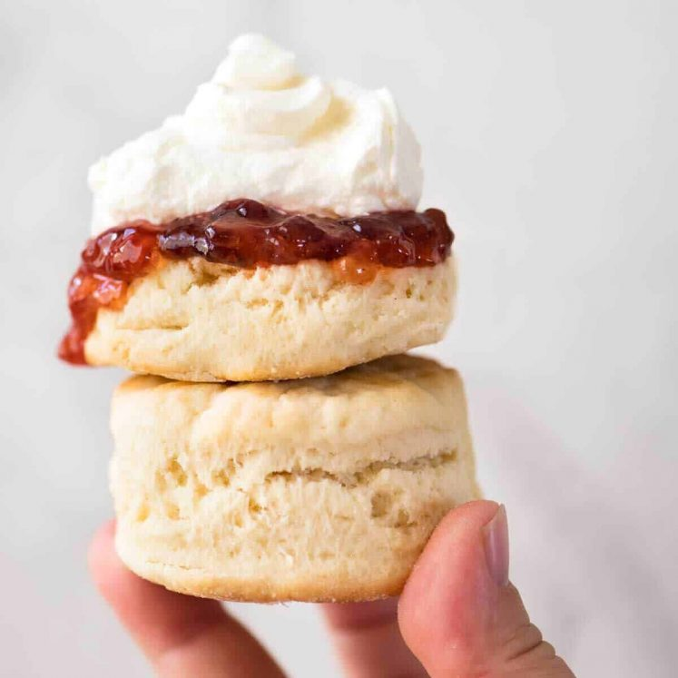 Close up of a plain scone with jam and cream being held up high, stacked on top of another scone.