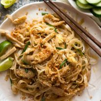 Overhead photo of Chicken Pad Thai on a rustic white plate with a side of cucumbers, ready to be eaten.