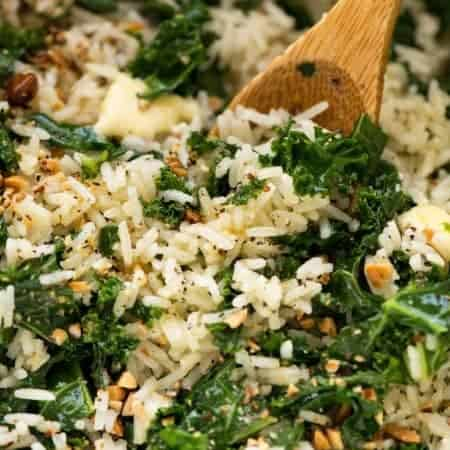 Close up of Garlic Butter Rice with Kale recipe in a pot with a wooden spoon, fresh off the stove ready to be served.