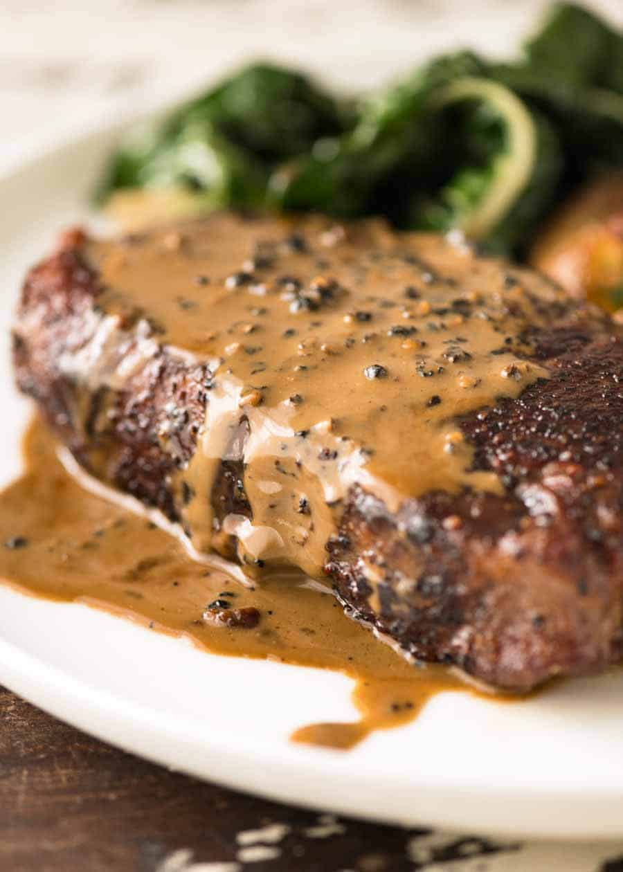 Close up of Creamy Peppercorn Sauce dripping down the side of steak