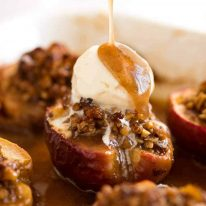 Close up of caramel sauce being drizzled over Baked Apples with ice cream on top in a baking dish, fresh out of the oven.