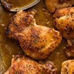 Close up of Crispy Garlic Chicken Thighs in a skillet with garlic butter sauce, ready to be served