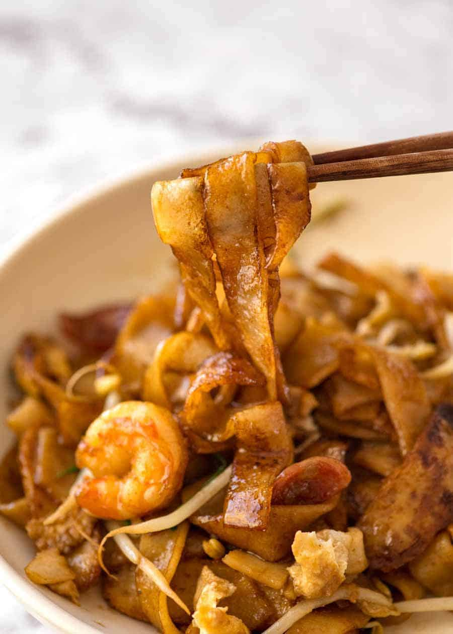 Close up of chopsticks pulling Char Kway Teow noodles out of a bowl