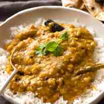 Homemade India lentil curry (Dal) served over rice in a rustic white bowl, ready to be eaten.