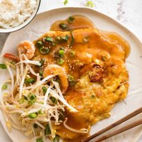 Overhead photo of Egg Foo Young on a rustic white plate with a side of rice, ready to be eaten