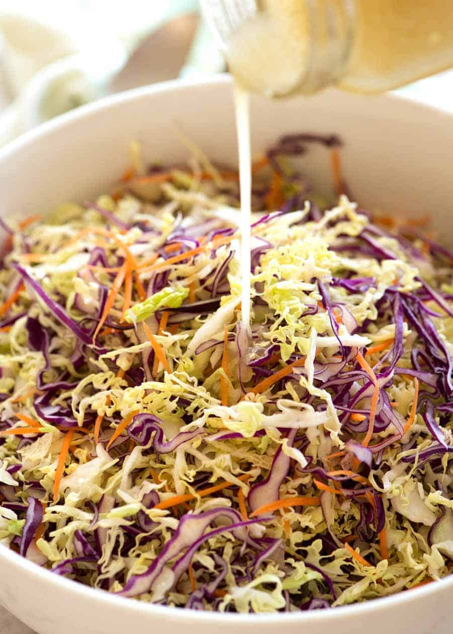Vinaigrette being poured over Everyday Cabbage Salad in a white bowl