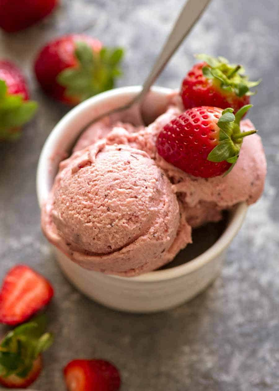 Creamy No Churn Strawberry Ice Cream in a small white dish topped with fresh strawberries, ready to be eaten