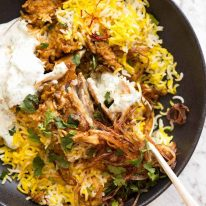 Chicken Biryani in a rustic black bowl with yellow saffron rice, garnished with crispy fried onions, coriander and minted yoghurt