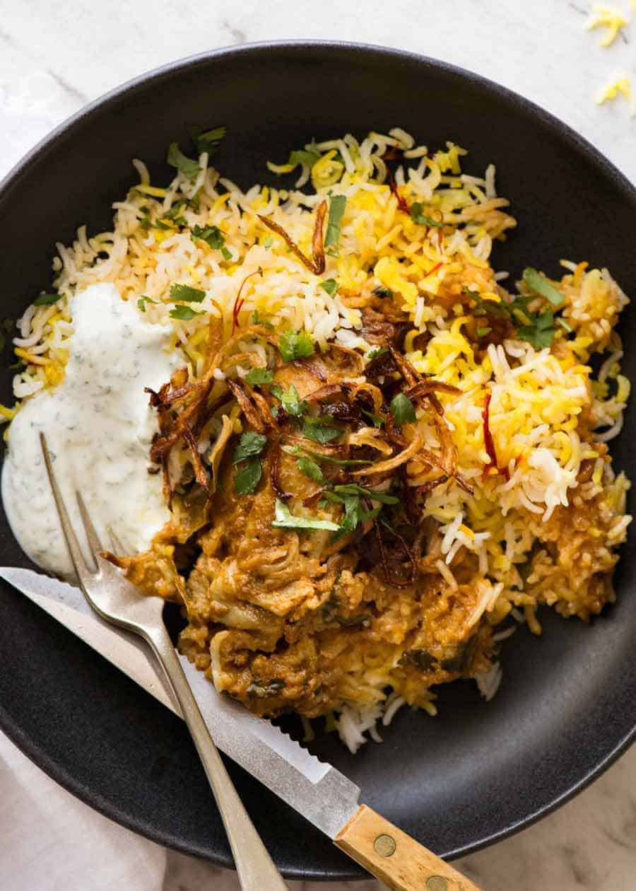Chicken Biryani in a rustic black bowl with yellow saffron rice, garnished with crispy fried onions, coriander and minted yoghurt, ready to be eaten